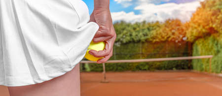 tennis ball in a womans hand in a skirt on a tennis court. preparation for serving a balloon in tennis. banner with copy space