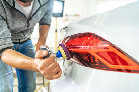 hand polishing car headlights with the help of a hand grinder for better shine