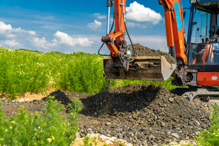 A small excavator is building a new road on a green field. copy space