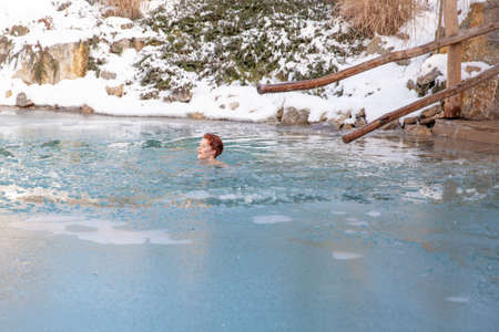 bathing young woman in a frozen lake after sauna.