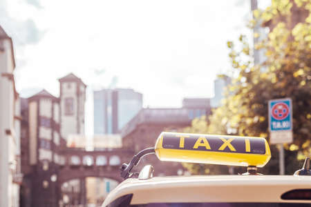 taxi car with a yellow sign on the roof in the city streets