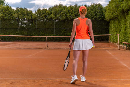 tennis ball in a womans hand in a skirt on a tennis court. preparation for serving a balloon in tennis