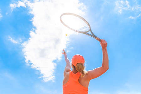 tennis serve by a young woman on the court. view from below