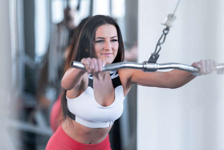 exercising with a pulley on a machine in the gym