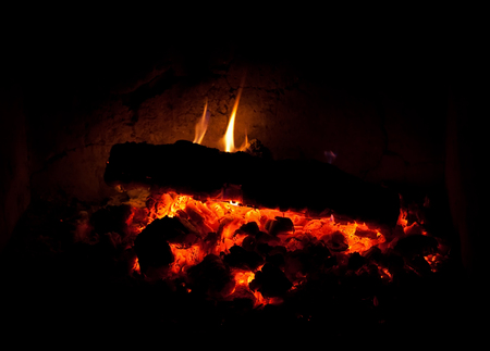 Photo of charcoal burning in the fireplace at night