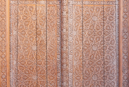 Carved wooden door at the Mir-i-Arab Madrasah at the Poi-Kalyan complex in the historic centre of Bukhara, Uzbekistan.