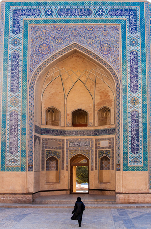 The main eastern entrance of the Kalon (Great) Mosque has a big portal decorated with mosaic. The portal is situated at a raised place and there are several steps leading to the mosque's courtyard. The Mosque was built circa 1514, and is part of the Po-i-Kalyan Complex in Bukhara, Uzbekistan Reklamní fotografie