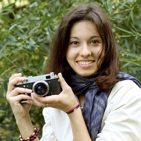 brown hair blue eyes: Beautiful girl with an old camera on nature background  Stock Photo