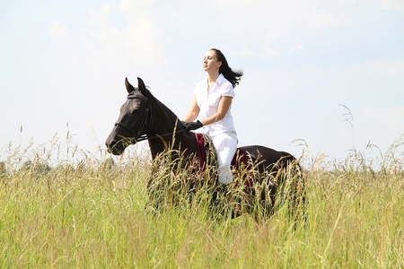 Young woman on horseback in the summer meadow photo