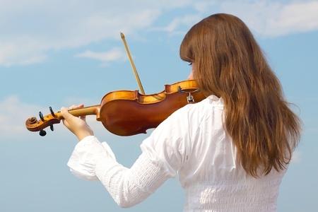 violist: Jonge vrouw speelt viool op hemelachtergrond Stockfoto