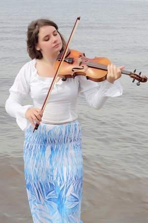 Young woman playing violin on sea background  photo