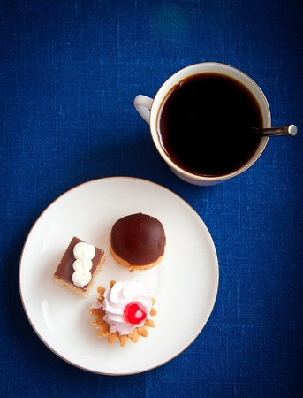 Cup of coffee and pastries on blue tablecloth. Top view.
