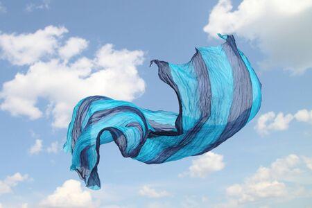 Flying silk piece against sky