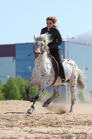 Mujer joven que monta un caballo con manchas