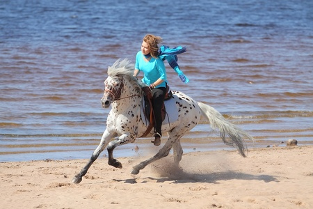 Girl in silk scarf rides a Altai horse of the shore of the Gulf of Finland