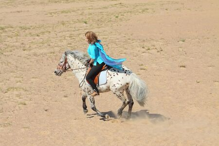 Beautiful girl rides a horse of Altai breed photo