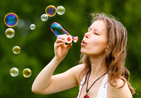 Beautiful young woman blowing soap bubbles outdoors Stock Photo - 14056672