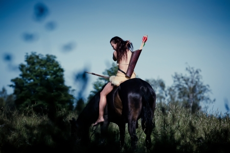 Young woman wearing clothes in amazon style on horseback photo