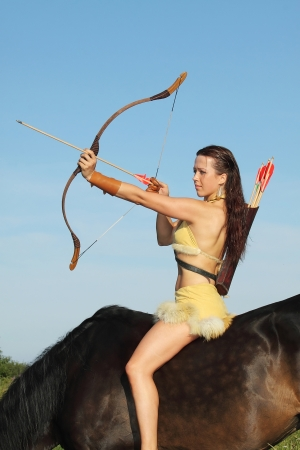 quiver: Young woman wearing clothes in amazon style on horseback