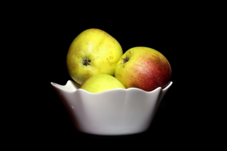 Three apples in the cup, isolated over black photo
