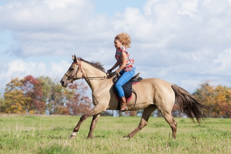 Girl riding a beautiful Akhal-Teke mare