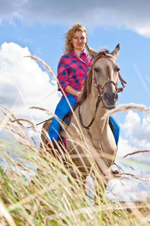 Young woman riding a beautiful Akhal-Teke mare on the meadow photo