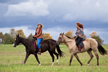 cola mujer: Dos chicas hermosas montar caballos Akhal-Teke Foto de archivo