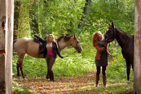 Two girls and two beautiful Akhal-Teke horses in an old park Stock Photo