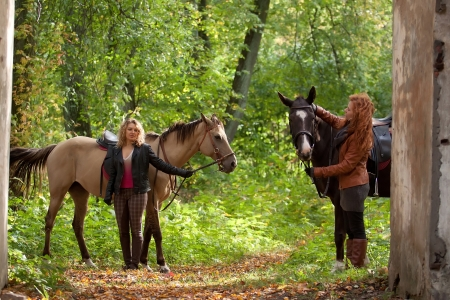 horse blonde: Two girls and two beautiful Akhal-Teke horses in an old park Stock Photo
