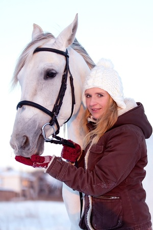 Beautiful young woman and Tersk stallion photo