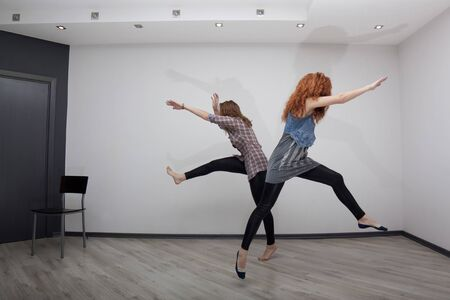 Two pretty girls having fun and jumping in an empty room Stock Photo - 17506641