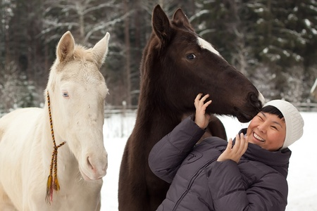 Young Asian woman and two horses outdoors photo