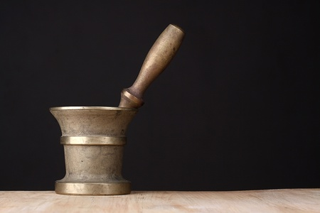 Old brass mortar with a pestle on a wooden table
