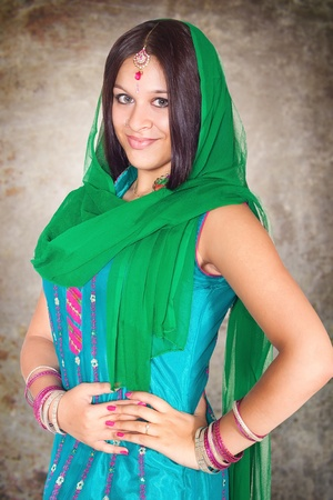 Beautiful Indian girl in traditional Indian clothing, on grunge background photo