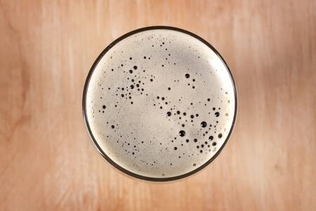 Glass of dark beer on table, top view