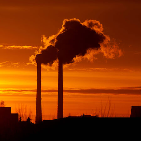 Industrial landscape with a smoke pipes at sunrise photo