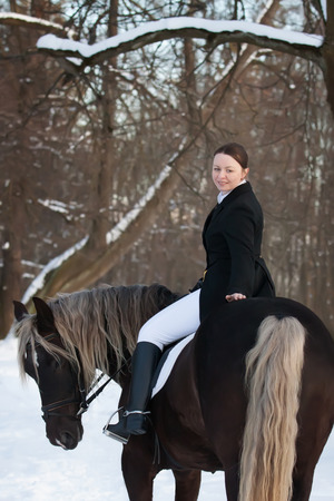 Young woman sits on horseback in spring forest photo