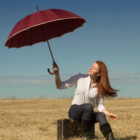 Beautiful red haired girl with vintage bag and umbrella outdoors photo