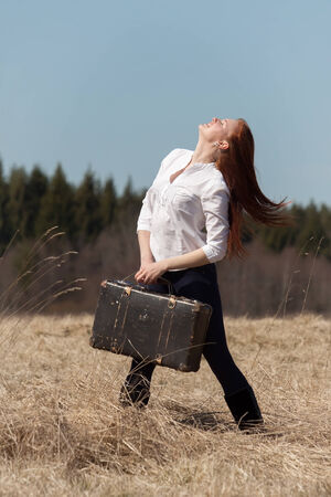 Red haired girl holding vintage bag in her hands photo