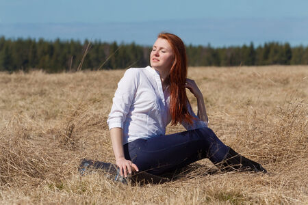 Red haired girl sitting on vintage bag in the springtime meadow photo