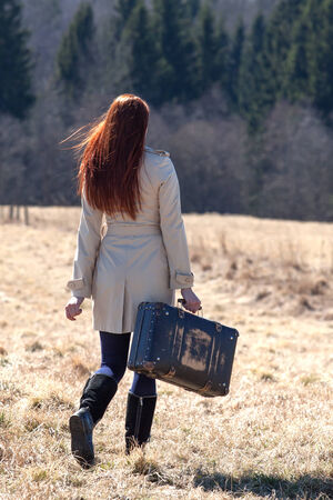 Beautiful red haired girl holding vintage bag photo