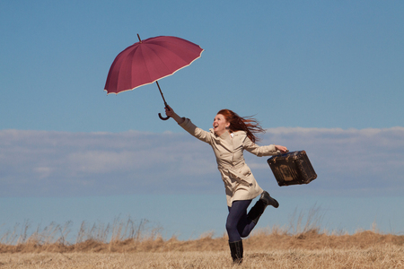 Red haired girl with vintage bag and umbrella  photo