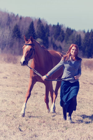 Beautiful red haired girl and Russian Don horse. Vintage effect. photo