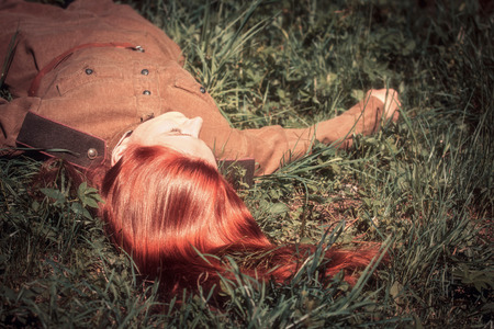 Young woman in Red Army form of 1943 year lying on the ground photo