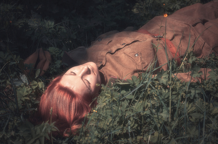 Young woman in Red Army form of 1943 year lying on the ground. Defocused effect of old photos. Stock Photo