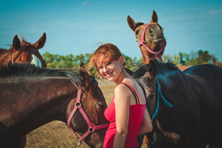 Young woman with herd of horses at autumn day. Retro photo effect. photo