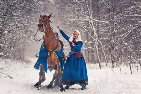 Young woman wearing medieval clothes and her horse. Interclub Association Cavalerie, St.Petersburg, Russia. photo
