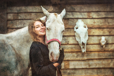 Young woman and her cremello horse on the background of horse and deer skulls photo