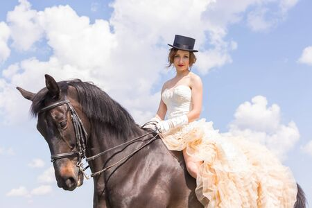 a frill: Pretty girl in vintage dress on horseback Stock Photo