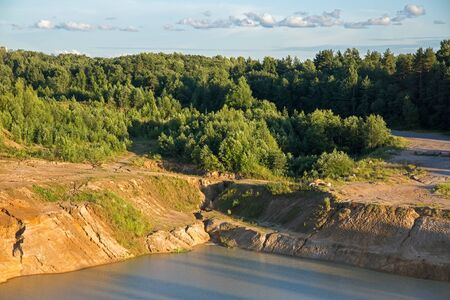 sand quarry: Sand quarry with a pond against blue sky